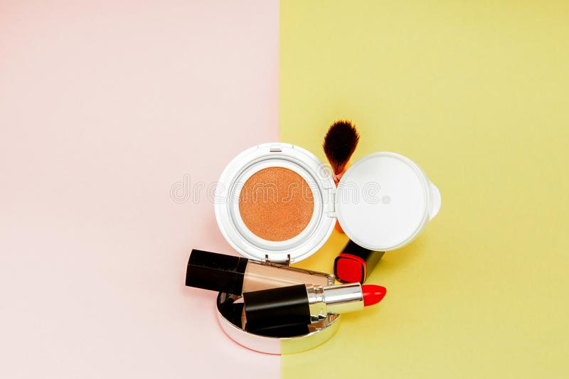 Make up products spilling on to a bright yellow and pink background with copy space. Minimal style royalty free stock photos