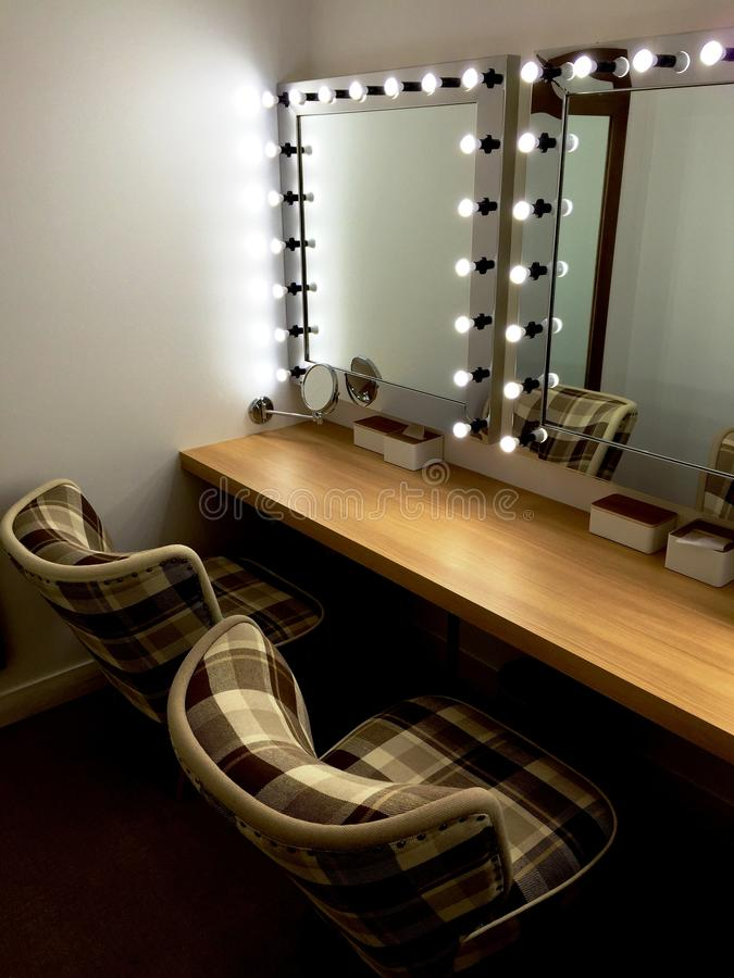 Make-up room with mirrors. A comfortable make-up room with light bulbs and soft tartan chairs royalty free stock image