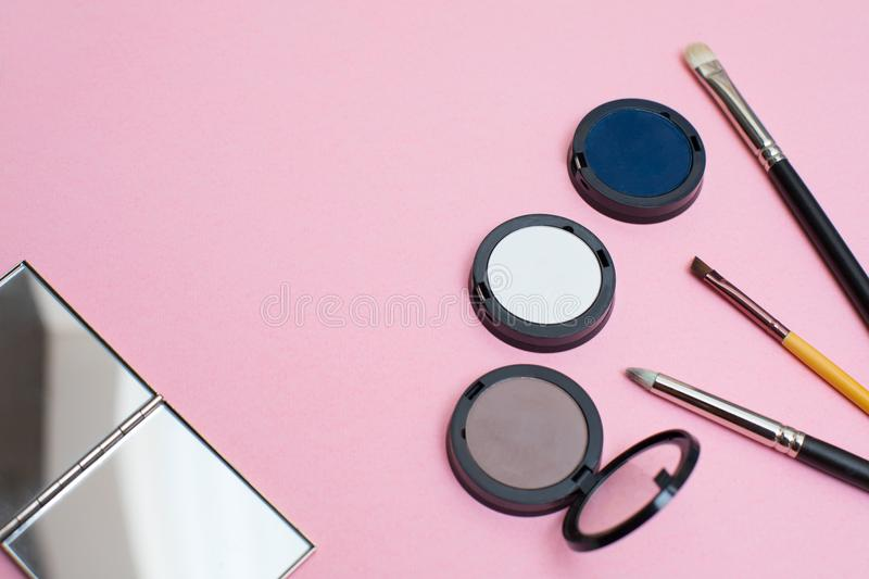 A make-up set on a pink background: makeup brushes, eyeshadows, and a mirror. Creative flat lay composition. royalty free stock photography