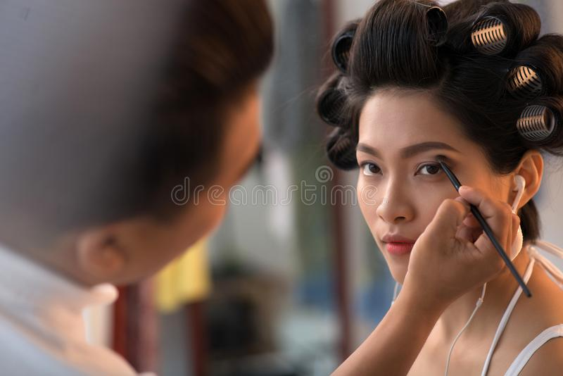 In make-up studio. Vietnamese young women having her make-up done at beauty salon stock photo