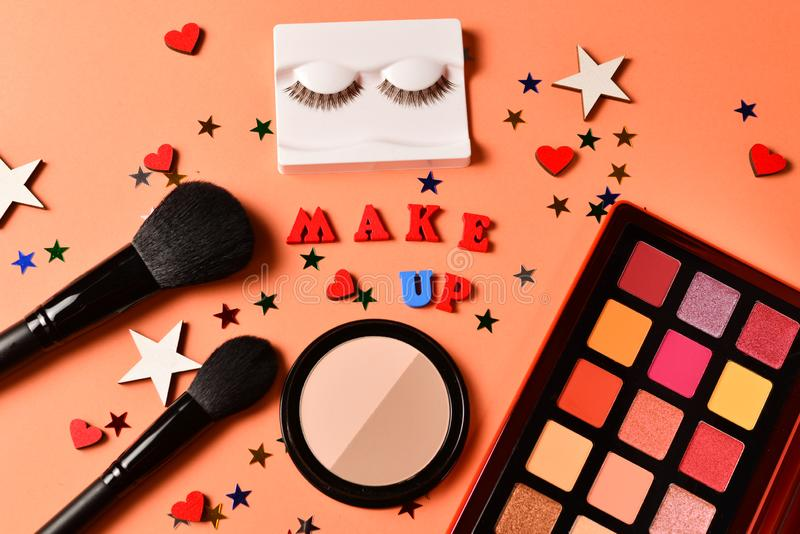 Make up text on an orange background. Professional trendy makeup products with cosmetic beauty products,  eye shadows, eye lashes stock photography