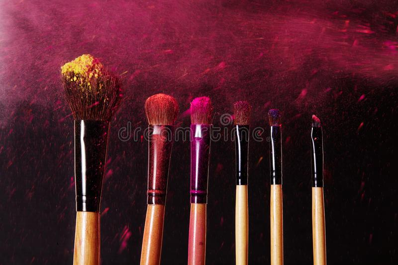 Make-up tools. Brush for makeup. Cosmetic brushes on black with bright dust splash. Colorful pink shadows pigment royalty free stock photos