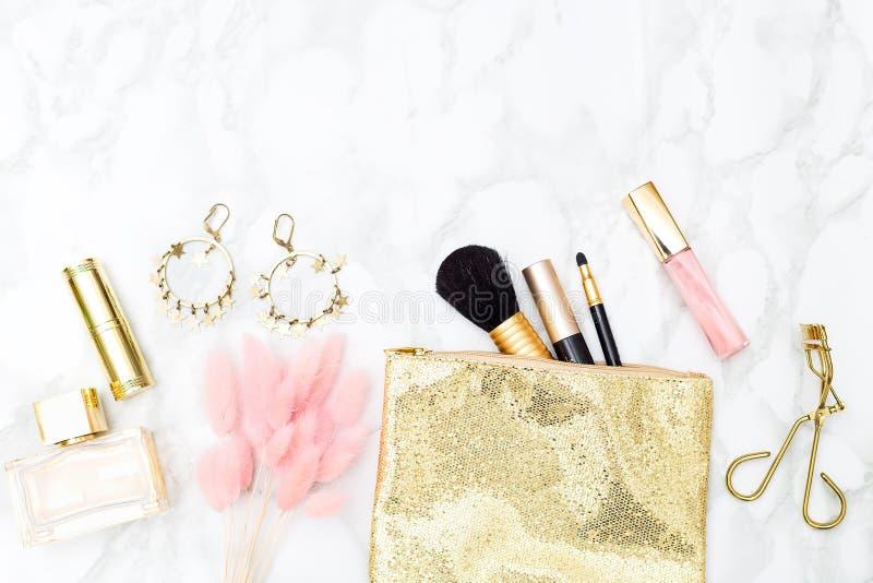 Make-up und Zubehörgold und -ROSA für Mädchen auf dem Tisch exemplar lizenzfreie stockfotografie