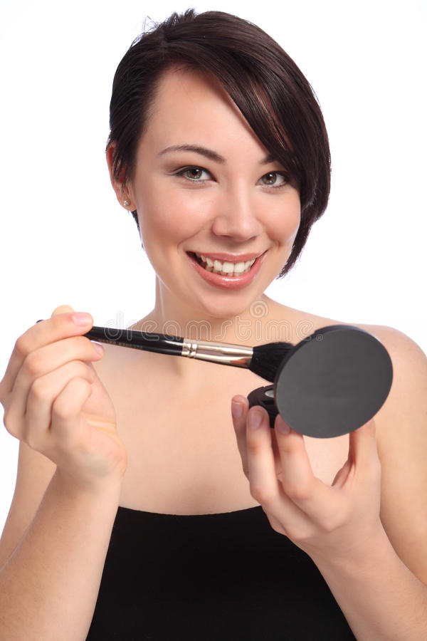 Make up using cosmetic compact and blusher brush stock photo