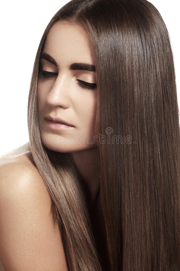 Make-up, wellness. Beautiful model with long shiny hair. Wellness. Ð¡osmetics. Portrait of woman with shiny long brown hair on gray background stock image