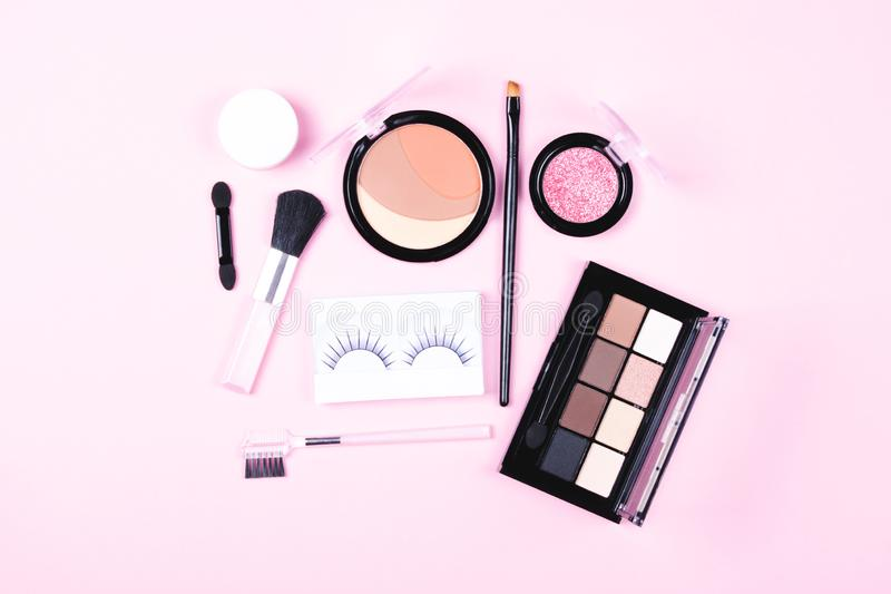 Make-up woman essentials on pink background. Make up woman essentials: decorative cosmetics, make-up accessories consisting of eye shadows, black applicator stock images
