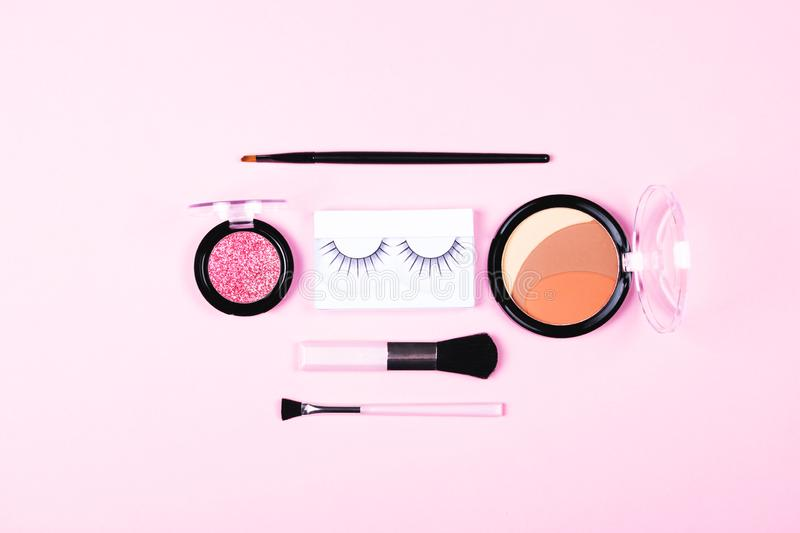 Make-up woman essentials on pink background. Make up woman essentials: decorative cosmetics, make-up accessories consisting of eye shadows, black applicator royalty free stock photo