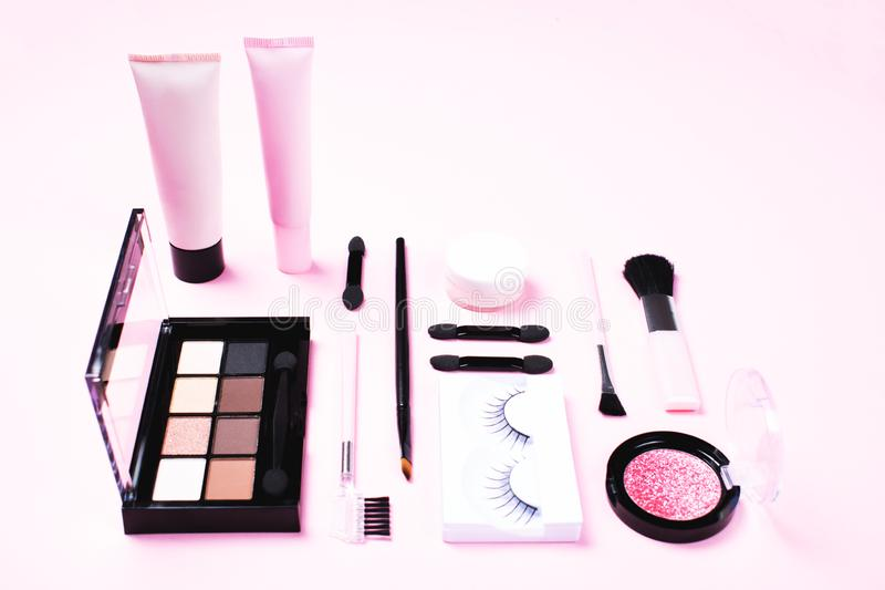 Make-up woman essentials on pink background. stock images