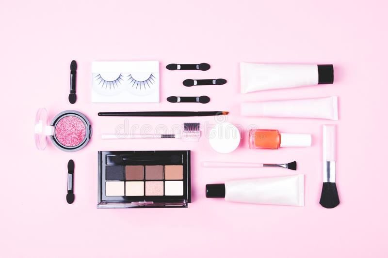 Make-up woman essentials on pink background. royalty free stock photography