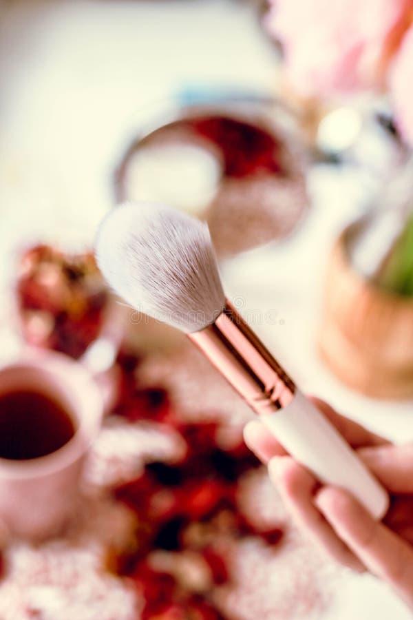 Make-upbürste in der weiblichen Hand mit unscharfem Hintergrund Erst-Person Ansicht stockfotografie