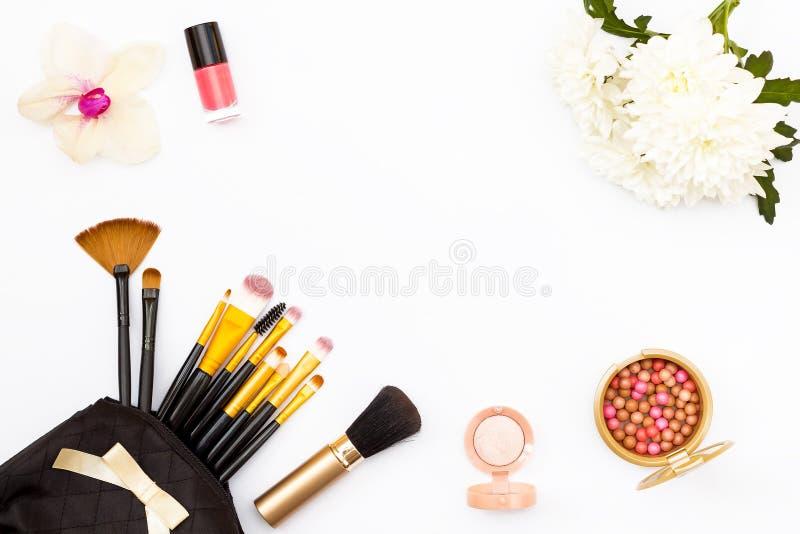 Make-upbürste in meinem Geldbeutel, Nagellack, Blumen, Chrysanthemen und Orchideen und andere Kosmetik auf einem weißen Hintergru stockfoto