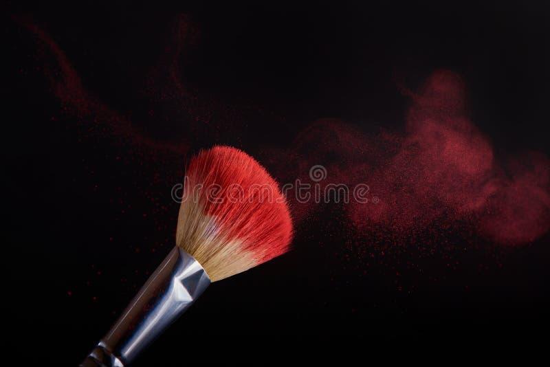 Make-upbürste mit roter Pulverexplosion auf schwarzem Hintergrund stockbild