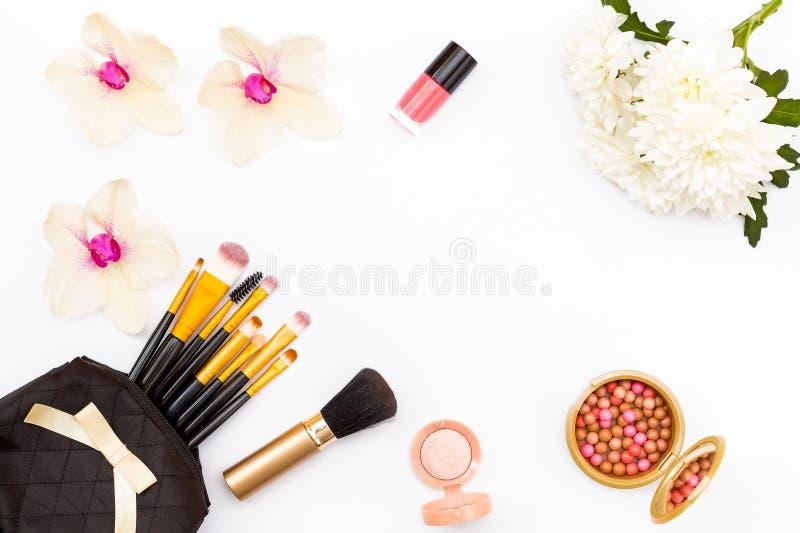 Make-upbürsten in der schwarzen Tasche, Blumen, Orchidee und Chrysantheme, Nagellack und andere Kosmetik auf einem weißen Hinterg stockfoto