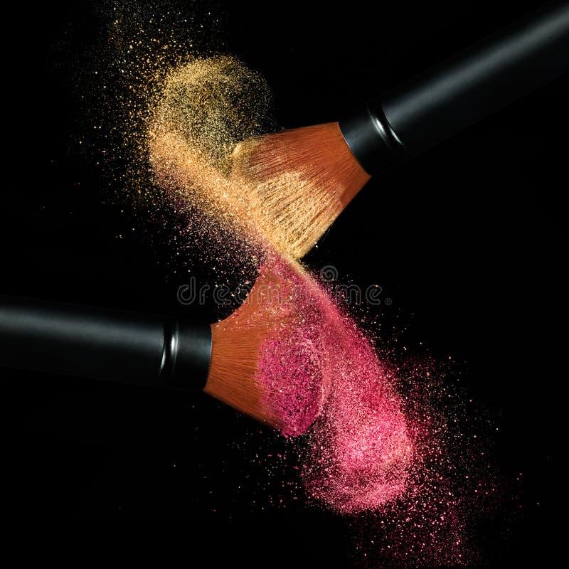 Make-upbürsten, die Pulver auf Schwarzem anwenden stockfotografie