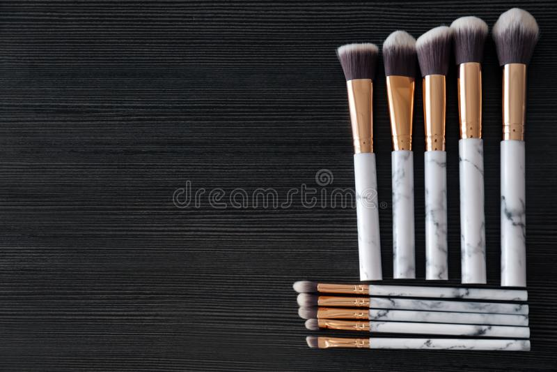 Make-upbürsten für das Auftragen von dekorativen Kosmetik auf dunklem hölzernem Hintergrund stockfotografie