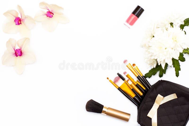 Make-upbürsten, rosa Nagellack, Orchidee und Chrysantheme blühen auf einem weißen Hintergrund Makrodetail des kosmetischen Behält stockfotografie