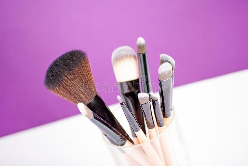 Make-upbürsten schließen oben auf purpurrotem Hintergrund stockfotografie