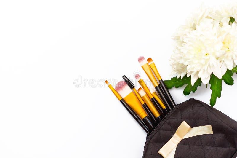 Make-upbürsten und eine Chrysantheme blühen auf einem weißen Hintergrund stockfotografie