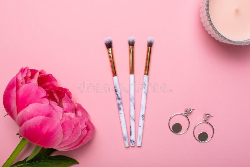 Make-upbürsten und -ohrringe der Frauen mit einer schönen Blumenpfingstrose auf einem rosa Hintergrund stockfotos