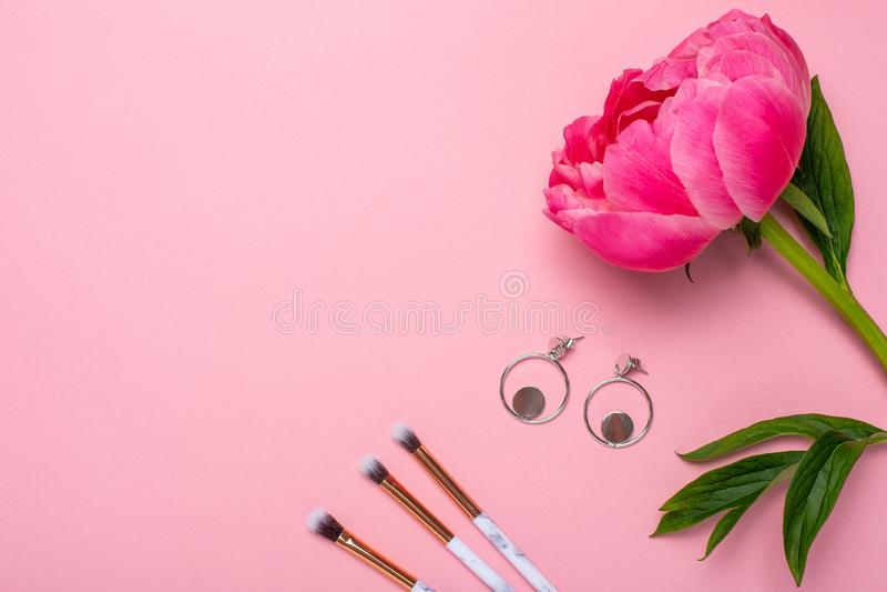 Make-upbürsten und -ohrringe der Frauen mit einer schönen Blumenpfingstrose auf einem rosa Hintergrund mit Kopienraum für Ihren T stockbild