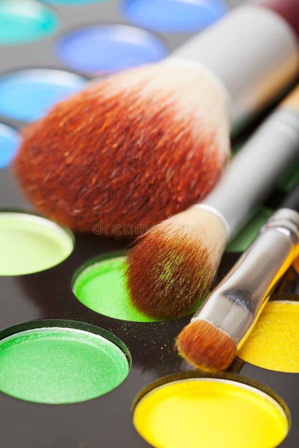 Make-upbürsten und Satz bunte Lidschatten stockfotos