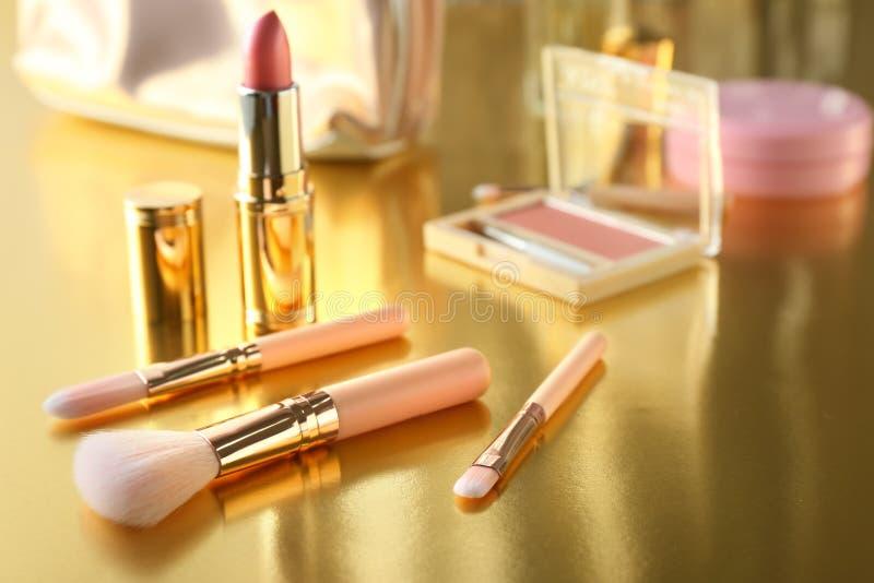 Make-upbürsten und rosa Lippenstift auf goldener Tabelle stockfotografie