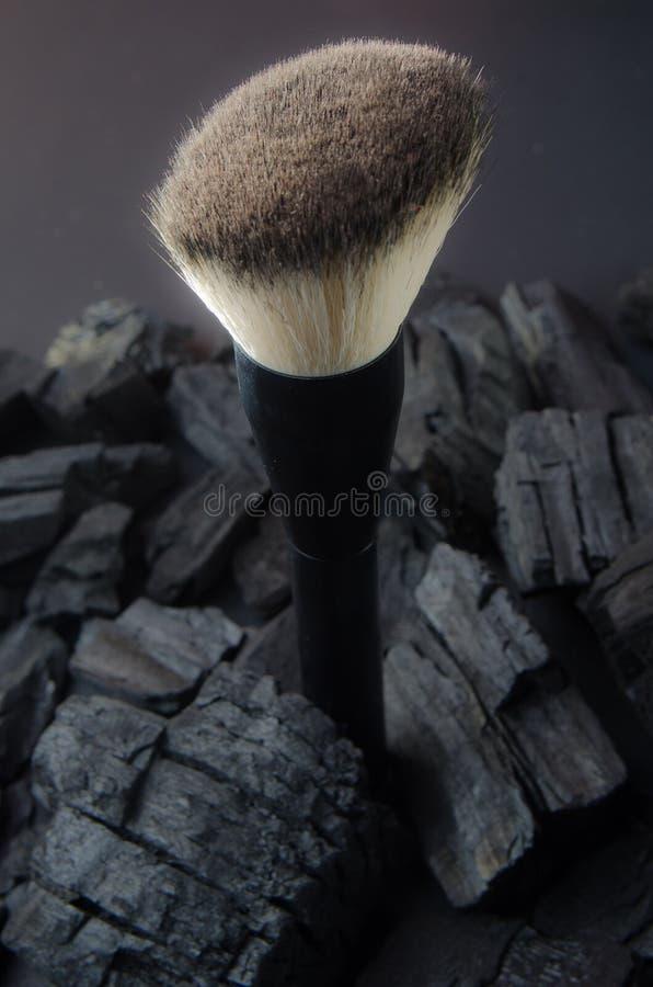 Make-upborstel door koolstoftextuur die wordt omringd stock foto's