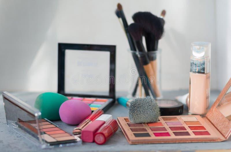 Make-upborstel en schoonheidsmiddelen op grijze lijst stock foto