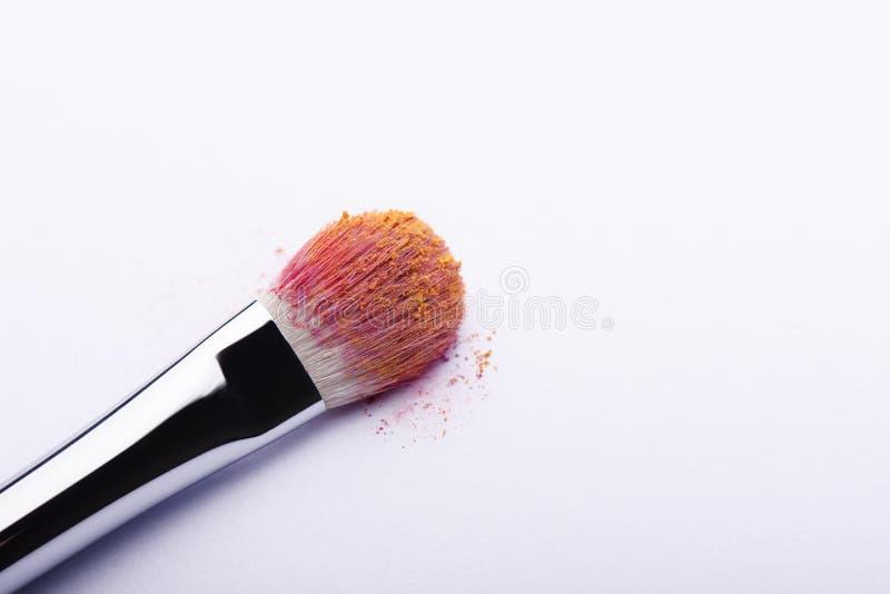 Make-upborstel in kleurrijk poeder op witte achtergrond royalty-vrije stock afbeeldingen