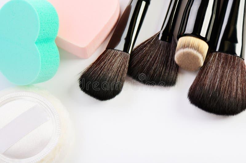 Make-upborstels, de vorm van het sponsenhart en poederdonsje op witte B royalty-vrije stock foto's