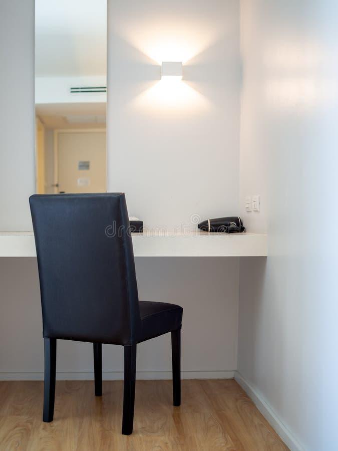 Make-upecke, schwarzer Stuhl, schwarzer Haartrockner vor dem Spiegel im Hotelzimmer stockfoto