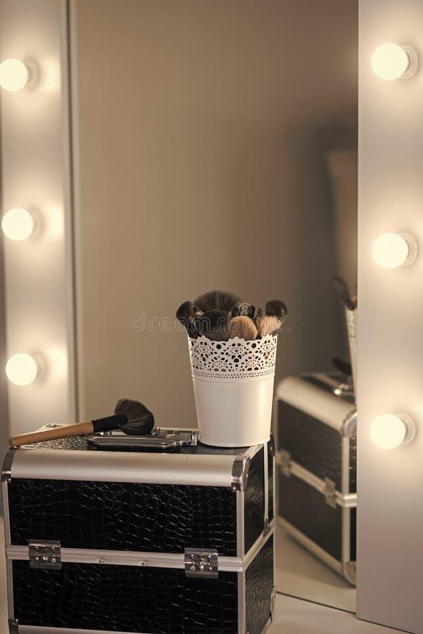Make-upgeval met borstels bij spiegel op toilettafel Professioneel maak omhoog uitrusting in schoonheidssalon Gezichtcursus, scho stock afbeelding