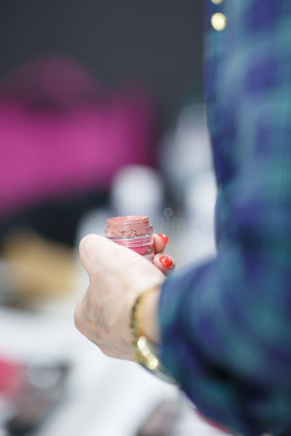 Make-upkünstler in der Hand hält Lippenstift Nahaufnahme lizenzfreie stockfotografie