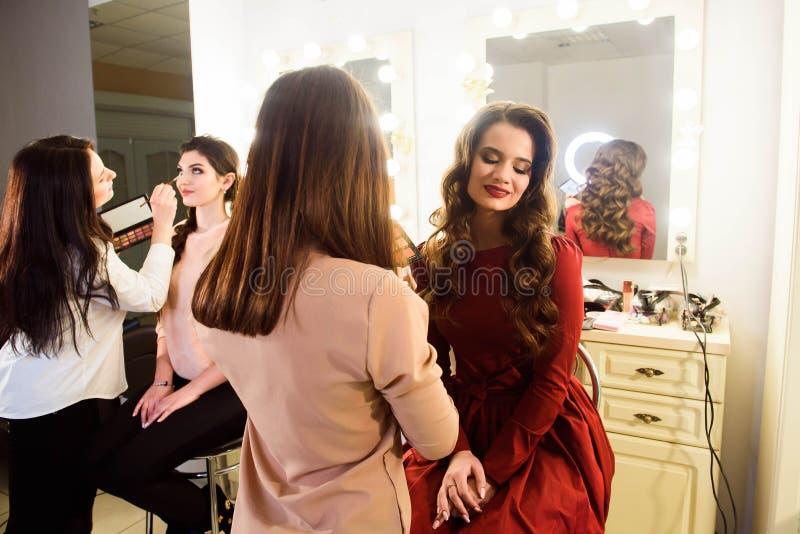 Make-upkünstler, der hellen niedrige Farblidschatten auf vorbildlichem ` s Auge anwendet und ein Oberteil mit Lidschatten auf Hin lizenzfreies stockbild