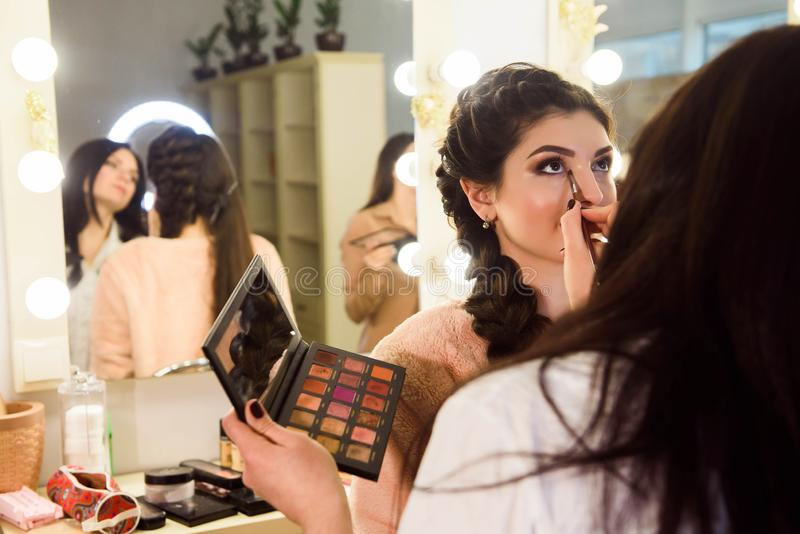 Make-upkünstler, der hellen niedrige Farblidschatten auf vorbildlichem ` s Auge anwendet und ein Oberteil mit Lidschatten auf Hin lizenzfreie stockfotografie
