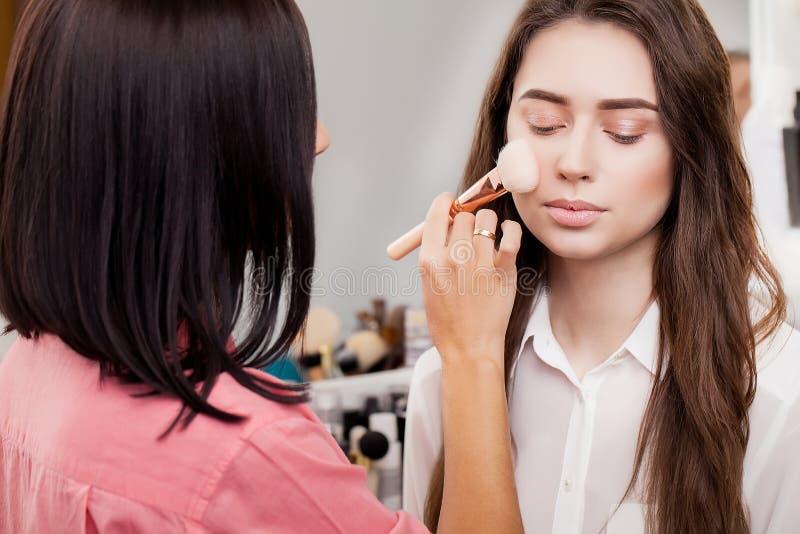 Make-upkünstler, der hellen niedrige Farblidschatten auf vorbildlichem ` s e anwendet lizenzfreie stockfotos