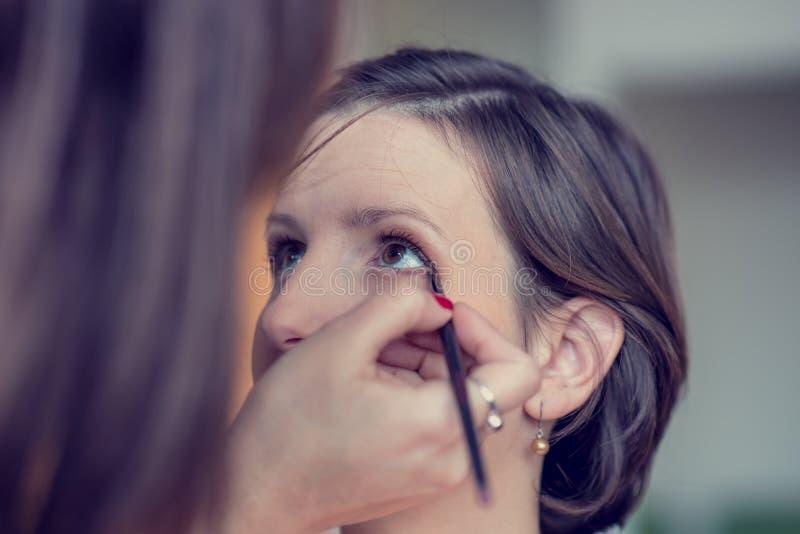 Make-upkünstler, der leichtes Make-up an einer Frau anwendet lizenzfreies stockbild