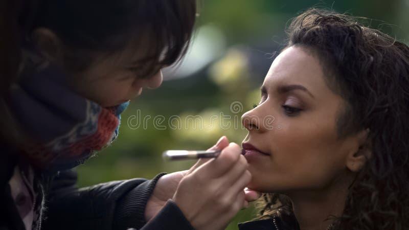 Make-upkünstler, der Lippenstift auf Modelllippen, Naturschönheit von biracial Dame anwendet lizenzfreie stockbilder