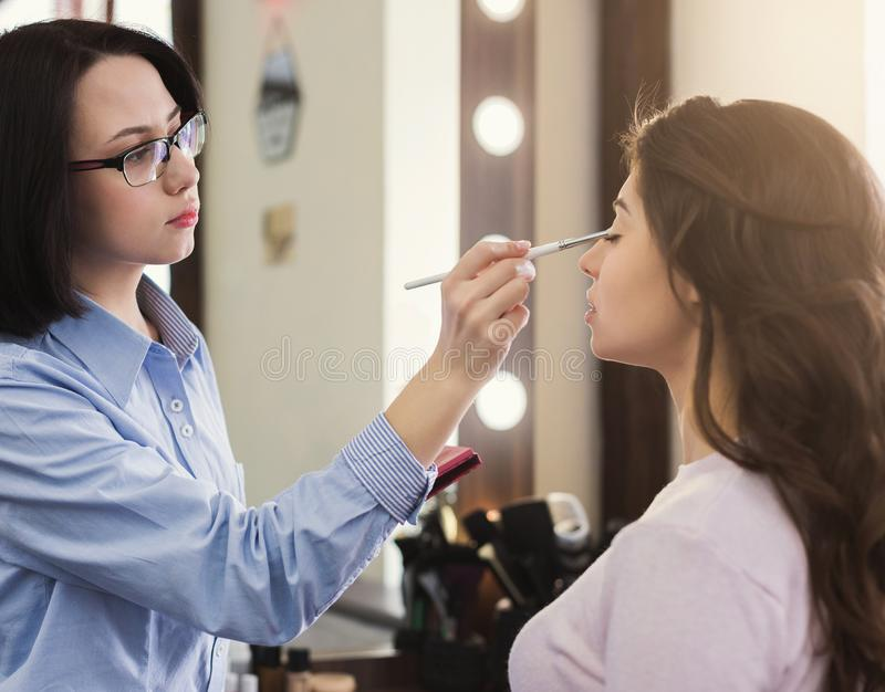 Make-upkünstler, der Make-up Mädchen im Salon antut stockbilder