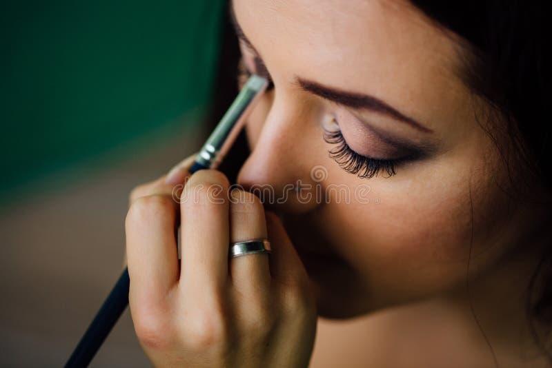 Make-upkünstlerhand, die helle niedrige Farbe auf vorbildlichem ` s Gesicht anwendet und eine Bürste, Abschluss hält stockfoto