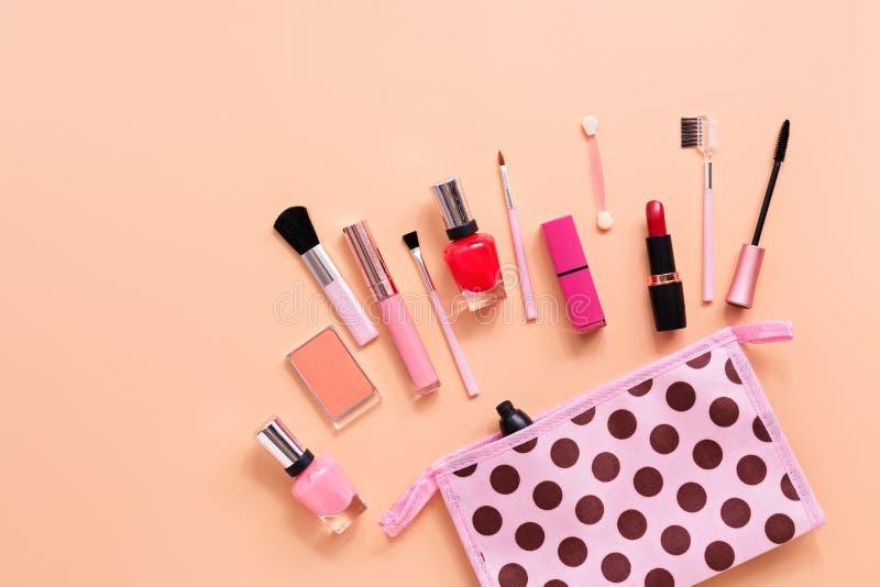 Make-upkosmetik der verschiedenen Frauen auf einem weichen rosa Hintergrund Kosmetiktasche, Rouge, Wimperntusche, Lippenstift, Na lizenzfreies stockbild