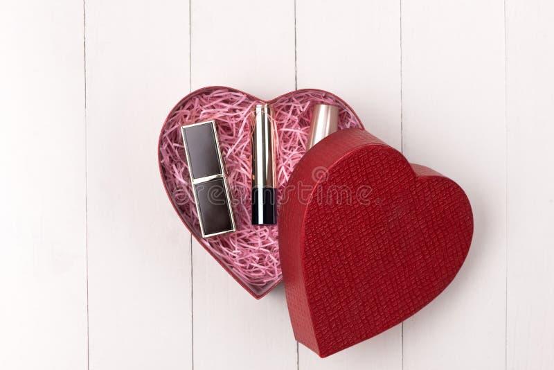 Make-upkosmetik im Herzformkasten auf Holztisch Fflat-Lage stockbilder