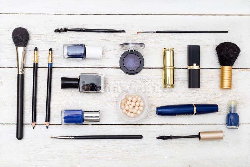 Make-upkosmetik verbreiteten heraus auf einem hölzernen Hintergrund Flache Lage lizenzfreies stockfoto