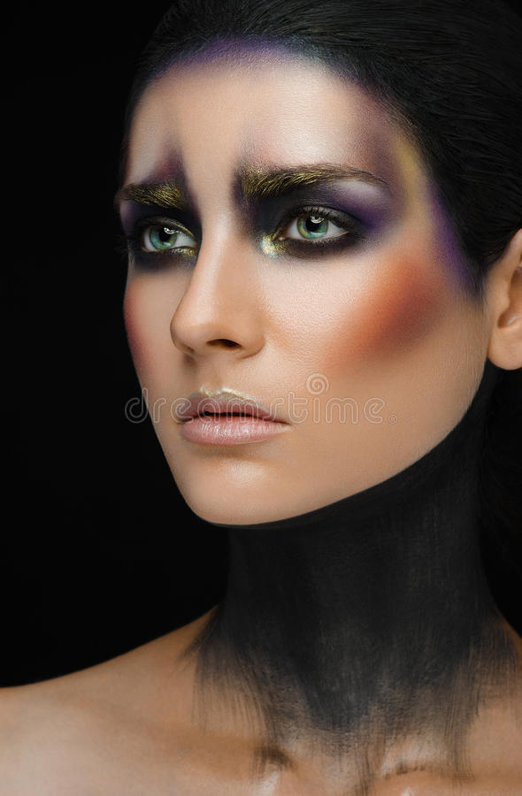 Make-upkunst en mooi modelthema: mooi meisje met een creatieve samenstellings zwart-en-purpere en gouden kleuren op een zwarte ba stock afbeeldingen
