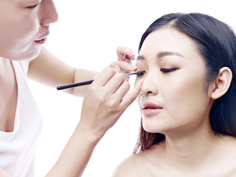 Make-upkunstenaar die aan een vrouwelijk Aziatisch model werken stock foto's