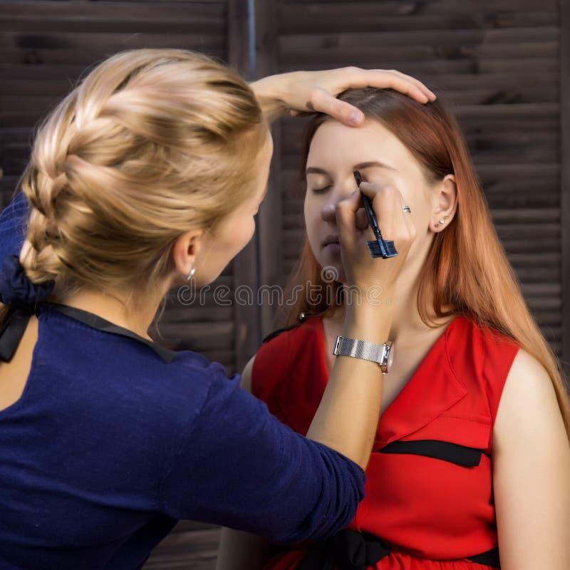 Make-upkunstenaar die jonge mooie vrouw voorbereiden close-upeyeliner stock afbeeldingen