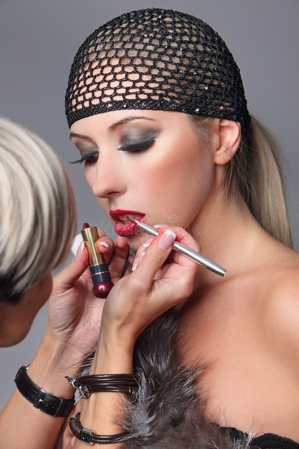 Make-upkunstenaar die lipgloss op gezicht van de vrouw toepassen Schoonheidsmeisje met make-uplipgloss en haarnetje royalty-vrije stock foto