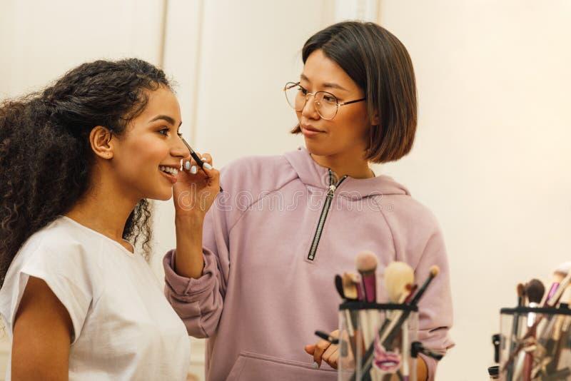 Make-upkunstenaar die makeover op een modelgezicht van toepassing zijn stock foto's