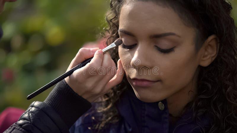 Make-upkunstenaar die oogschaduw op ogen van model of actrice, schoonheidsblog toepassen stock afbeelding