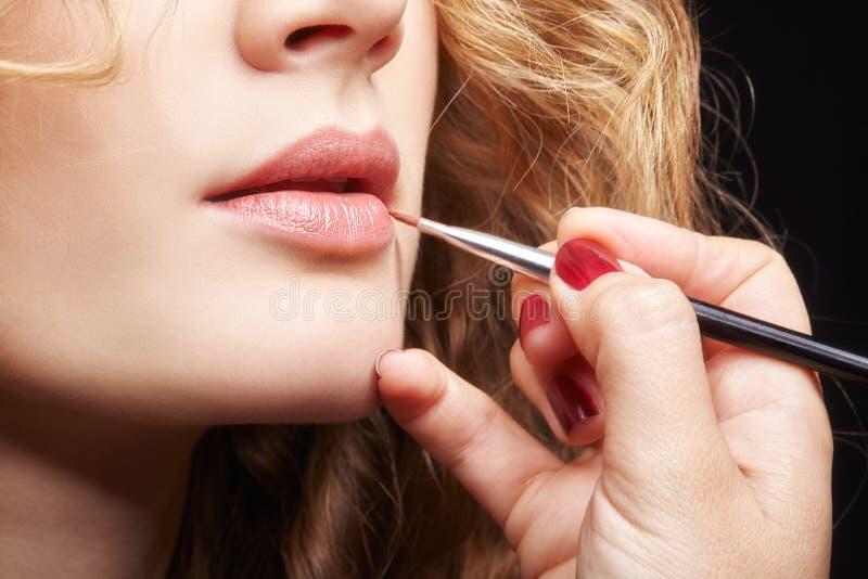 Make-upkunstenaar die visagiste borstel voor toepassingslippenstift gebruiken op lippen van jong Kaukasisch model met golvend gem stock foto